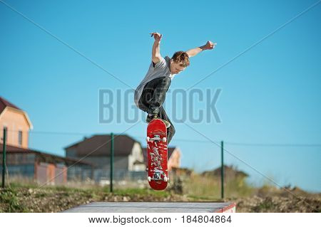 A teenager skateboarder does an ollie trick in a skatepark on the outskirts of the city On a background of houses and a blue sky