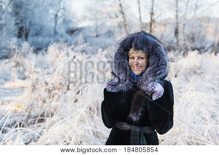 Winter landscape, girl with blond hair and short hairstyle in a black fur coat on a background river under the ice and tree branches covered with white frost