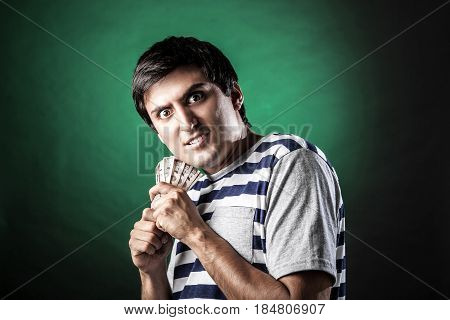 Man with bills in hands with expression of greed and smug