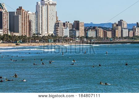 Surfers Surfing On Sea Against City Skyline In Durban