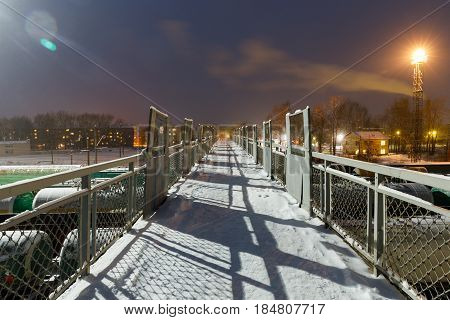 footbridge over Freight cars on the sorting cargo station in the light of searchlights at night in winter in Russia