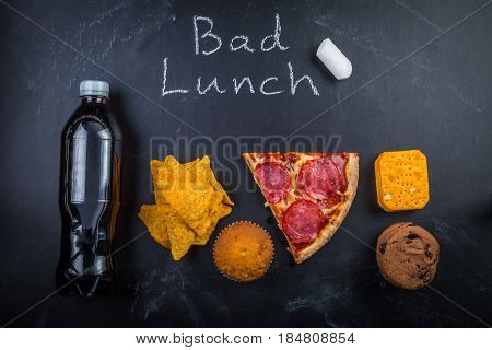 Unhealthy school lunch, isolated on dark board