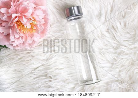 Styled mockup of clear plain glass water bottle on white faux fur with a flower. Custom gifts.