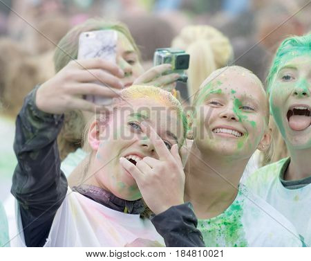 STOCKHOLM SWEDEN - MAY 22 2016: Three smiling teenage girls covered with green color dust in the Color Run Event in Sweden May 22 2016