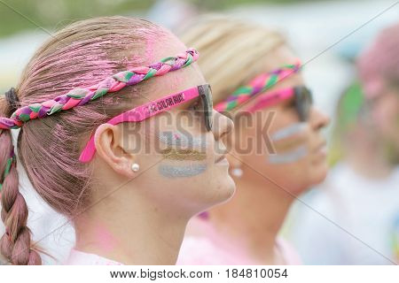 STOCKHOLM SWEDEN - MAY 22 2016: Side view of the face of a young beautiful woman with silver and gold color dust in her face in the Color Run Event in Sweden May 22 2016