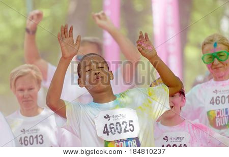STOCKHOLM SWEDEN - MAY 22 2016: Happy children and adults with pink color dust in their face and arms up in the Color Run Event in Sweden May 22 2016