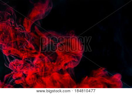 Abstract background red smoke texture in the air. Smoke fragments isolated on dark background.
