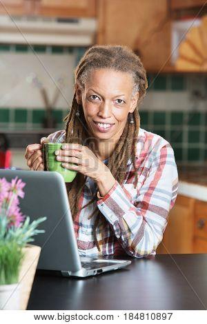 Beautiful Woman Holding Coffee Mug Next To Laptop
