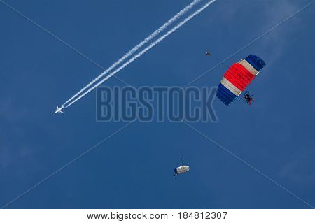 Two Parachutists fly to the sky. One tandem with parachutists in the air. On the sky flying. A large airliner flies high and creates white traces in the blue sky. Paragliders on a blue sky background. Tandem parachute jump.