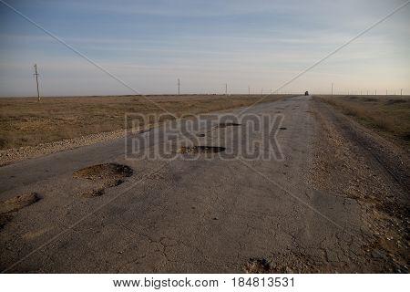 Broken cracked road with potholes in Kazakhstan