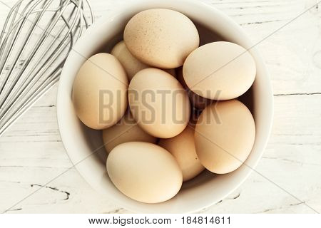 Eggs in white bowl.  Top view with whisk.