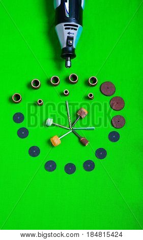 A gray drill with drilling accessories on green background aerial view.
