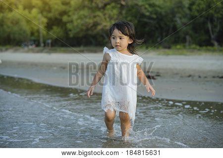 children walking on the beach at the sun shining beach in Thailand.