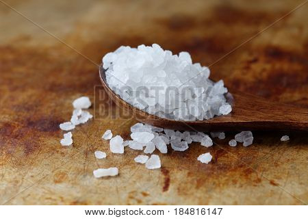Himalayan Halite salt condiment macro view. Natural mineral flavoring food preservative, Saline sodium chloride white crystal in wooden spoon, aged rusty background. Shallow depth field.
