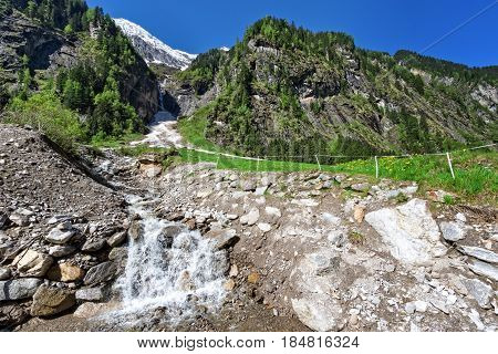 Snow melting mountain landscape with a brook in the springtime