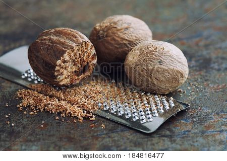 Making nutmeg powder. Macro view silver grater with grated muscat nuts. Kitchen still life photo. Shallow depth of field, retro rusty background. Selective focus.