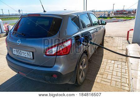Samara Russia - April 30 2017: Pumping gasoline fuel in passenger car at gas station