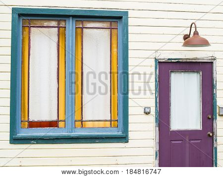 Purple door with lamp above and green window in need of repaint in weatherboard wall.