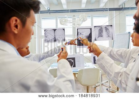 Radiologists discussing together x-ray images and analyzing them