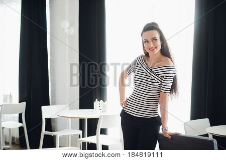 Cheerful woman in a cafe looking through a window. Happy attractive lady smiling and looking away
