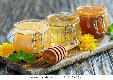 Different Varieties Of Honey In Glass Jars.