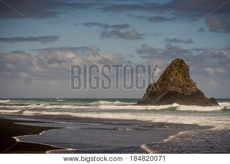 Auckland New Zealand - March 2 2017: Black sand Karakare Beach under blue cloudy sky with Te Kaka Whakaara Rock (Watchman) in the surf of Tasman Sea.