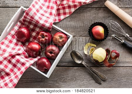 Ripe red apples in birch tray on wooden board with red checkered napkin around accessories for baking and copy space for your text.