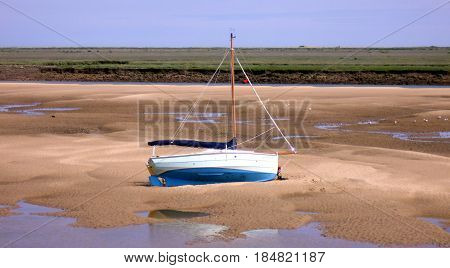 Boat on Sand Bank at East Fleet Estuary at The Quay in Wells-next-the-Sea in Norfolk
