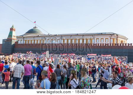 Moscow, Russia - May 9, 2016: Immortal Regiment procession in Victory Day - thousands of people marching along the Red Square with flags and portraits in commemoration of their loved ones who fought in World War Two