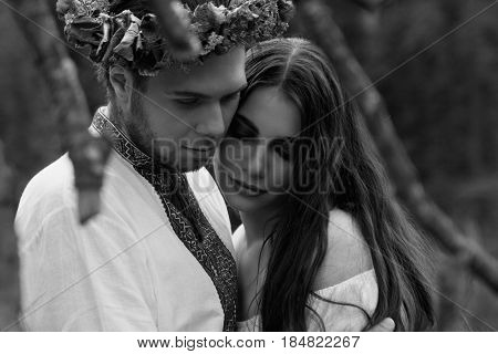 Guy hugs young beautiful girl at folk festival. Folk style. Close-up view. Black and White