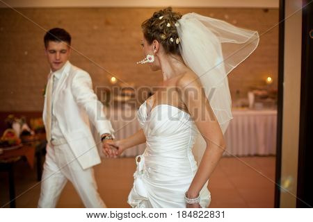 Bride Turns Over Her Shoulder Walking With A Groom