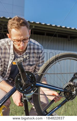Young handsome man is tuning the bike chain. Outdoor. Vertical photo