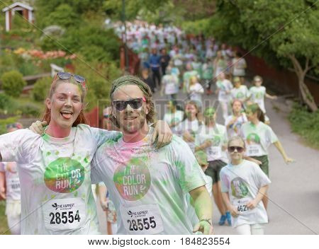 STOCKHOLM SWEDEN - MAY 22 2016: Happy smiling teenage couple covered with colorful color dust in the Color Run Event in Sweden May 22 2016