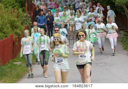 STOCKHOLM SWEDEN - MAY 22 2016: Group of running happy smiling teenagers covered with colorful color dust in the Color Run Event in Sweden May 22 2016