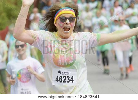 STOCKHOLM SWEDEN - MAY 22 2016: Jumping happy smiling senior woman covered with colorful color dust in the Color Run Event in Sweden May 22 2016
