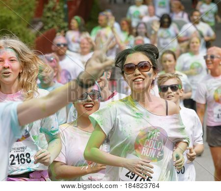 STOCKHOLM SWEDEN - MAY 22 2016: Group of running happy smiling girsl covered with colorful color dust in the Color Run Event in Sweden May 22 2016
