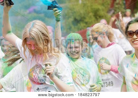 STOCKHOLM SWEDEN - MAY 22 2016: Happy smiling teenage girls squirting colorful color dust in their hair in the Color Run Event in Sweden May 22 2016