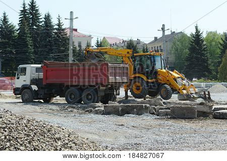 Ukraine. Ternopil. Outdoor exterior repair work. 05.04.2017 The tractor loads a stone in a dumper