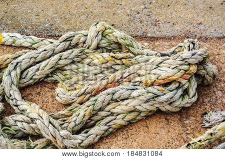 Old Faded Rope Lying On The Shore In A Fishing Port, Industry Equipment, Seaside Town