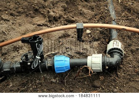 Horticultural irrigation pipe fittings on garden soil