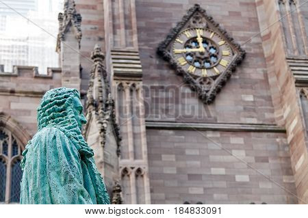 New York April 28 2017: Sculpture of John Watts on the Trinity Church's cemetery in Manhattan with a large clock in the background.