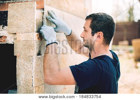 Male Mason Worker Installing Stone Tiles On House Facade. Construction Details Worker