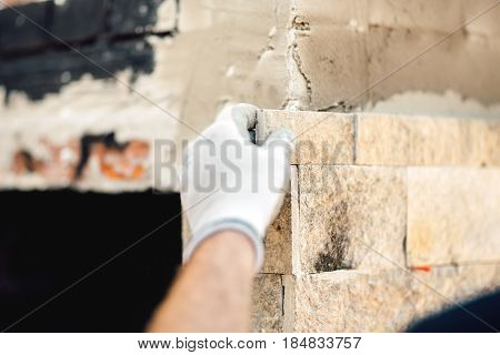 Close Up Details Of Worker Hands Using Cement And Stone. Construction Mason Worker At Work