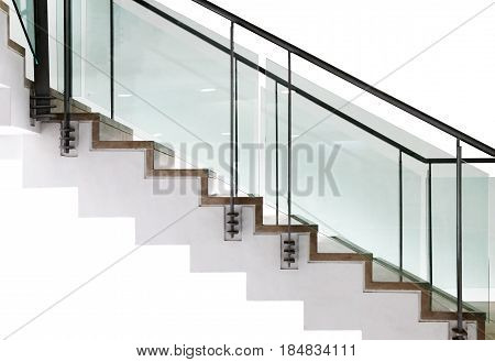 Modern staircase with glass panels against a white wall