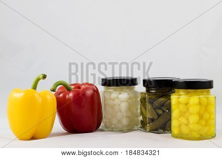 Red and yellow peppers preserves and olive oil in the pantry