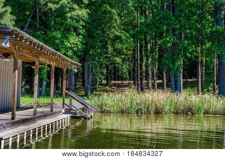 Boat house, dock resting in reflective lake waters.  Scenic outdoor setting or trees, grass and water.  Relax or enjoy sporting activity including swimming or fishing from lake dock.