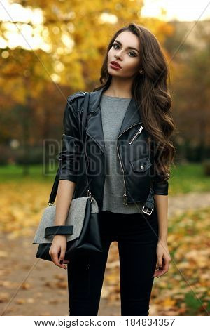 Beautiful stylish girl in gray pullover, black jeans and leather jacket standing and posing in autumn park. Pretty young woman with long curly brunette hair and red lips holding handbag