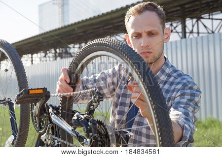 A concentrated craftsman is diagnosing bike malfunctions on the street