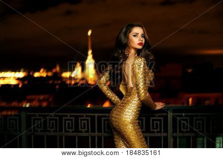 Sexy fashionable beautiful young woman in long golden shining evening dress standing at balcony over view on night city lights in bokeh. Pretty lady with long curly hair and red lips