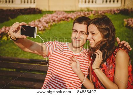 Young Beautiful Couple Sitting On The Park Bench And Taking Self Portrait With Smartphone On Beautif
